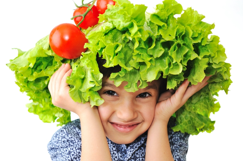 Kid with salad and tomato hat on his head, fake hair made of veg